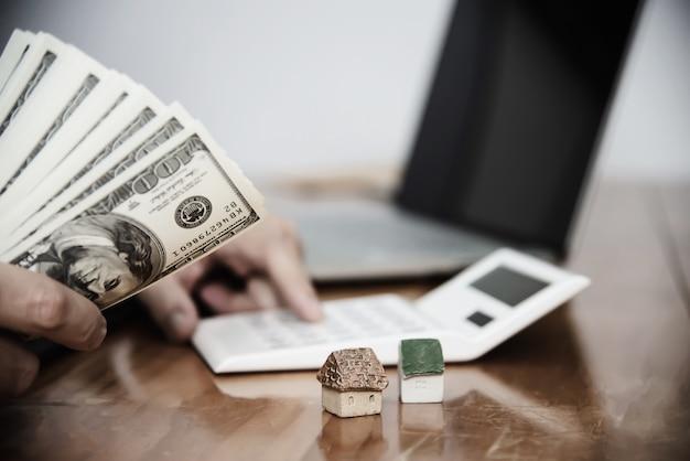 La banconota dei soldi di manifestazione dell'uomo di affari fa il piano finanziario invita la gente a vendere o comprare la casa e l'automobile - concetto di assicurazione di credito di prestito di proprietà monetarie Foto Gratuite