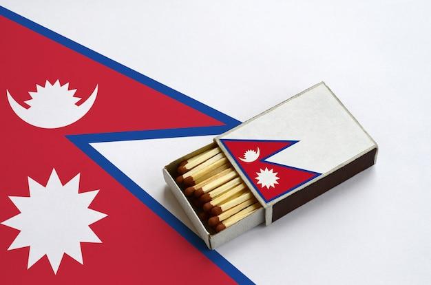 La bandiera del nepal è mostrata in una scatola di fiammiferi aperta, che è piena di fiammiferi e si trova su una grande bandiera Foto Premium