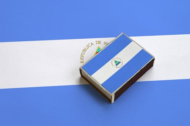 La bandiera del nicaragua è raffigurata su una scatola di fiammiferi che si trova su una grande bandiera Foto Premium
