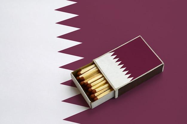 La bandiera del qatar è mostrata in una scatola di fiammiferi aperta, che è piena di partite e si trova su una grande bandiera Foto Premium