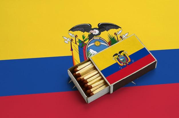La bandiera dell'ecuador è mostrata in una scatola di fiammiferi aperta, che è piena di fiammiferi e si trova su una grande bandiera Foto Premium