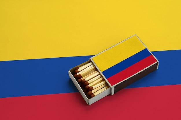 La bandiera della colombia è mostrata in una scatola di fiammiferi aperta, che è piena di fiammiferi e si trova su una grande bandiera Foto Premium