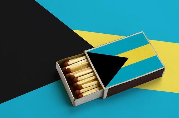 La bandiera delle bahamas è mostrata in una scatola di fiammiferi aperta, che è piena di fiammiferi e si trova su una grande bandiera Foto Premium