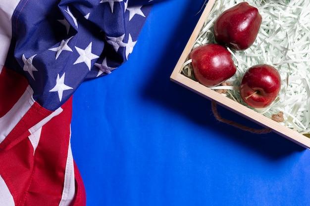 La bandiera unita dello stato d'america e le casse di legno per la frutta della mela sul blu Foto Premium