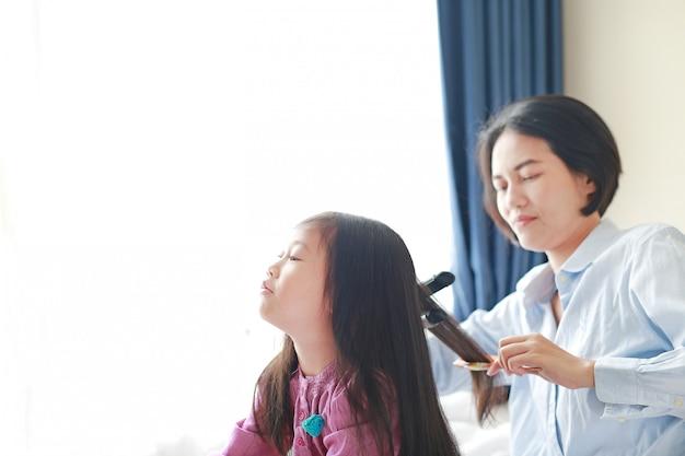 La bella bambina asiatica del bambino con capelli lunghi e la mamma si sono agghindati per capelli lisci alla mattina nella stanza. Foto Premium