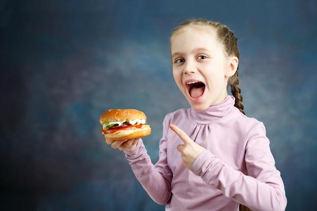 La bella bambina caucasica sveglia è mostra un hamburger in sua mano Foto Premium