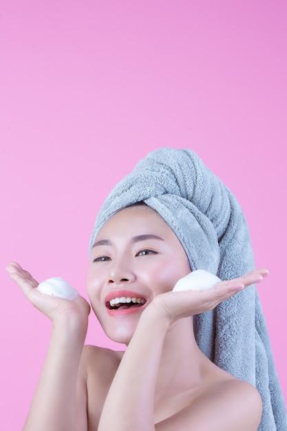 La bella donna asia sta lavando il suo fronte su fondo rosa. Foto Gratuite