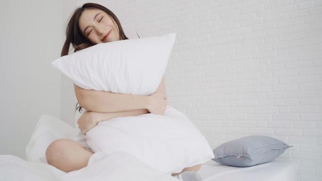 La bella donna asiatica felice sveglia, sorridendo e allungando le sue armi nel suo letto nella camera da letto. Foto Gratuite