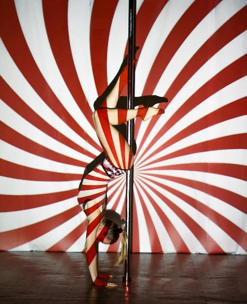 La bella donna balla vicino ad un palo su una priorità bassa a strisce. Foto Premium