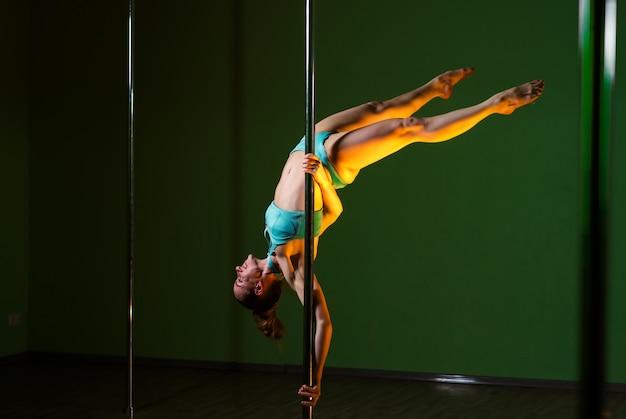 La bella donna balla vicino ad un palo su una priorità bassa colorata. Foto Premium