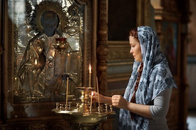 La bella donna caucasica russa con i capelli rossi e una sciarpa in testa è nella chiesa ortodossa, accende una candela e prega davanti all'icona. Foto Premium