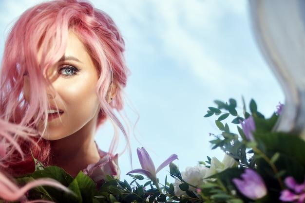 La bella donna con capelli rosa tiene grande mazzo con verde e fiori viola Foto Gratuite