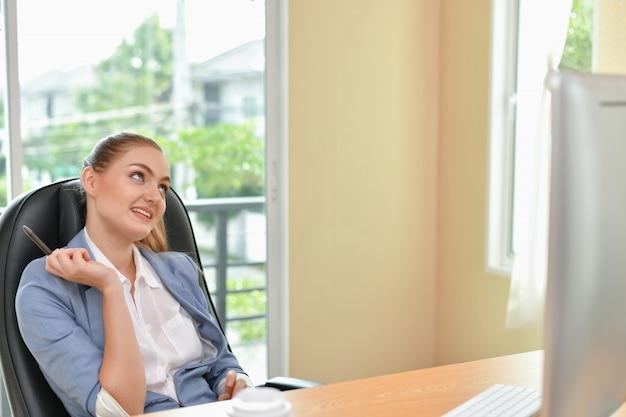 La bella donna di affari sta lavorando in ufficio Foto Premium