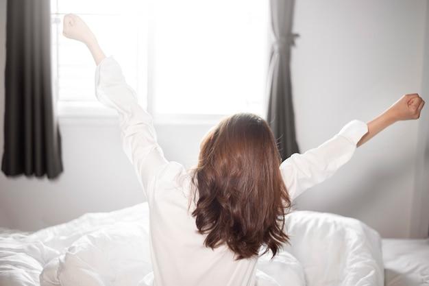 La bella donna è svegliarsi sul letto in mattinata Foto Premium