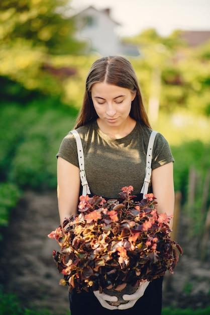 La bella donna lavora in un giardino vicino alla casa Foto Gratuite
