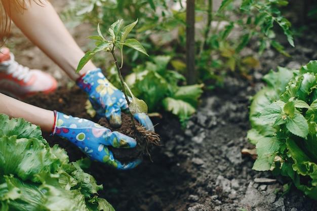 La bella donna lavora in un giardino Foto Gratuite