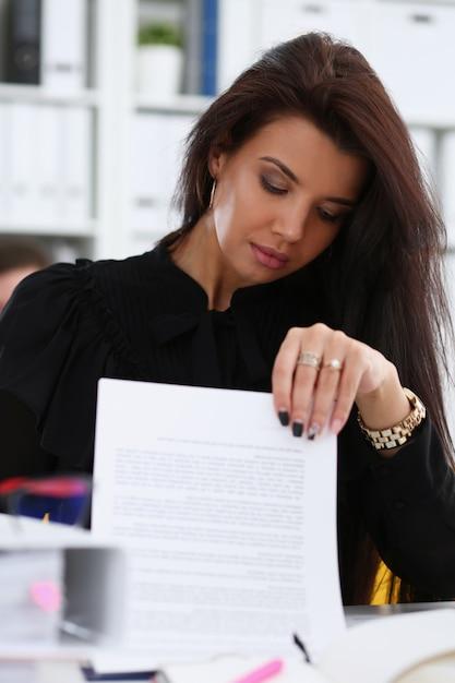La bella donna sorridente del brunette si siede alla tabella Foto Premium