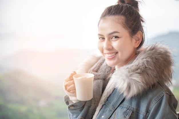 La bella donna sta bevendo il caffè di mattina con il fondo della natura Foto Premium