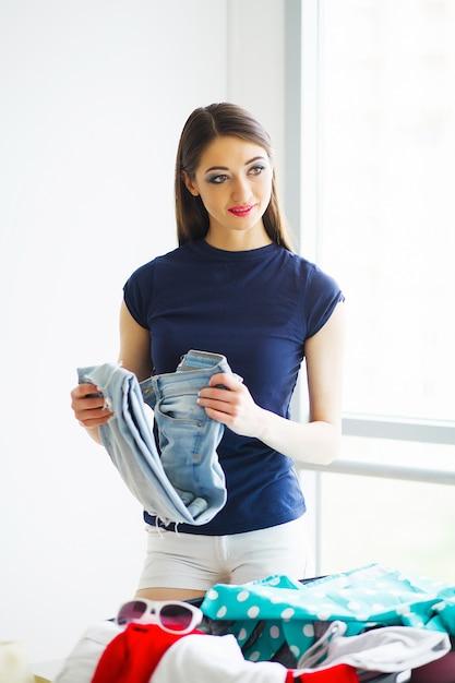 La bella donna sta imballando i vestiti in valigia a casa Foto Premium