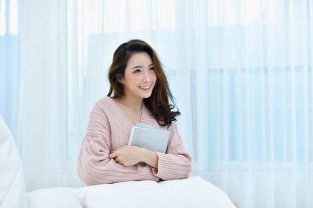 La bella donna sta rilassando in una camera da letto bianca. Foto Premium