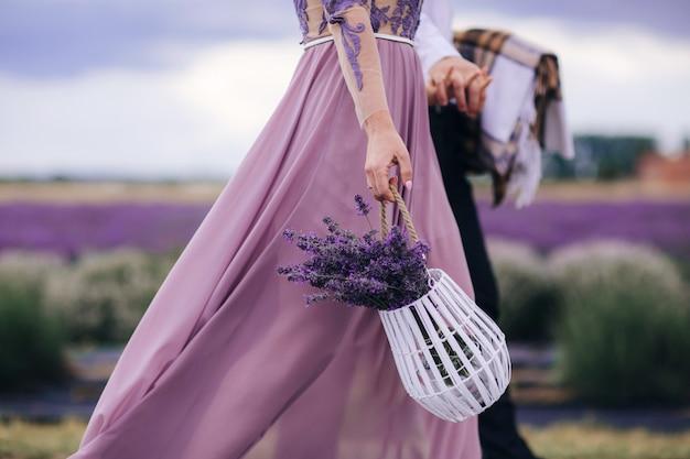 La bella donna tiene il mazzo della merce nel carrello della lavanda dei fiori mentre cammina all'aperto attraverso il giacimento di grano di estate. Foto Premium