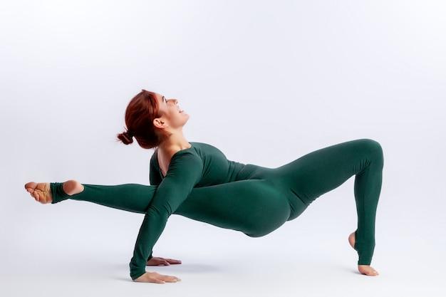 La bella ginnasta della giovane donna in calzamaglia attillate solleva la sua gamba sopra la sua testa per allungare e sorride su bianco Foto Premium