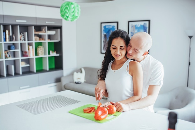 La bella giovane coppia macina insieme le verdure nella cucina. Foto Premium