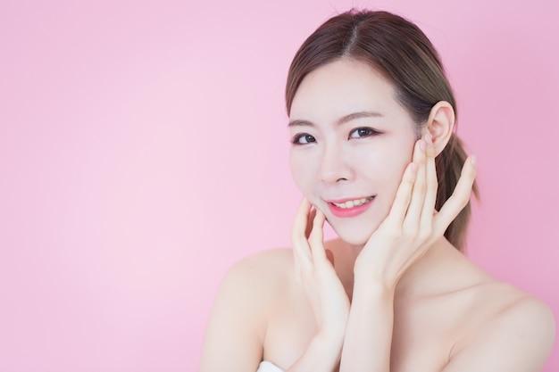 La bella giovane donna asiatica caucasica tocca il suo fronte pulito della pelle fresca. cosmetologia, cura della pelle, pulizia della faccia Foto Premium