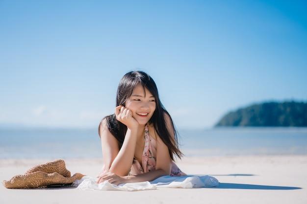 La bella giovane donna asiatica che si trova sulla spiaggia felice si rilassa vicino al mare. Foto Gratuite