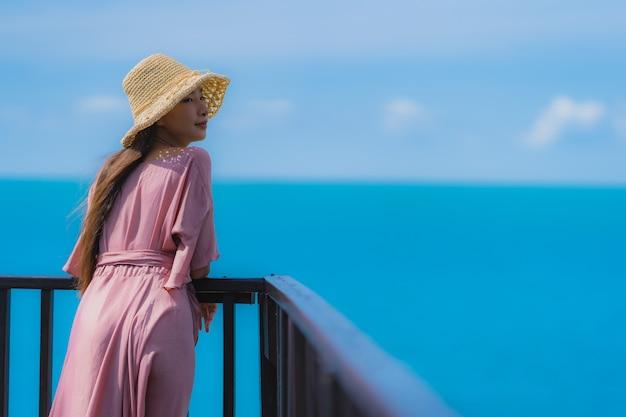 La bella giovane donna asiatica del ritratto che guarda l'oceano della spiaggia del mare per si rilassa nel viaggio di vacanza di festa Foto Gratuite