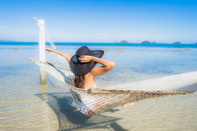 La bella giovane donna asiatica del ritratto che si siede sull'amaca intorno all'oceano della spiaggia del mare per si rilassa Foto Gratuite