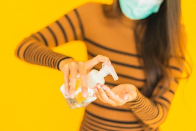 La bella giovane donna asiatica del ritratto con lo spruzzo dell'alcool della maschera e il gel imbottigliano la sua mano per proteggono da coronavirus o covid19 Foto Gratuite