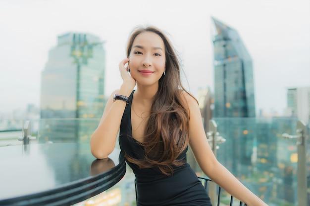 La bella giovane donna asiatica del ritratto si rilassa gode del ristorante sul tetto Foto Gratuite