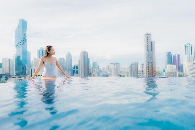 La bella giovane donna asiatica del ritratto si rilassa lo svago felice di sorriso intorno alla piscina all'aperto Foto Gratuite