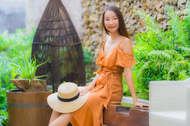 La bella giovane donna asiatica del ritratto si rilassa sulla sedia intorno al giardino Foto Gratuite