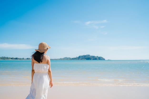 La bella giovane donna asiatica felice si rilassa camminando sulla spiaggia vicino al mare. Foto Gratuite