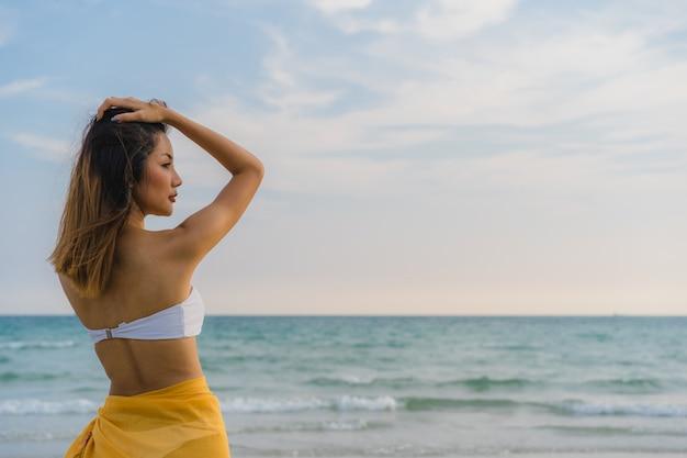 La bella giovane donna asiatica felice si rilassa la camminata sulla spiaggia vicino al mare. Foto Gratuite
