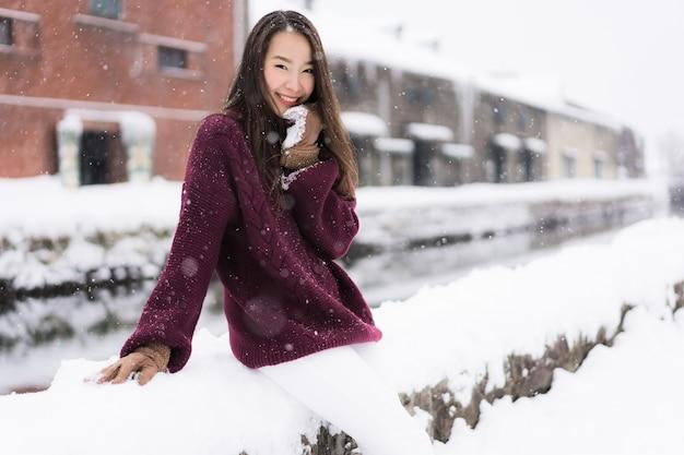 La bella giovane donna asiatica sorride e soddisfatta del viaggio di viaggio nel canale hokkaido giappone di otaru Foto Gratuite