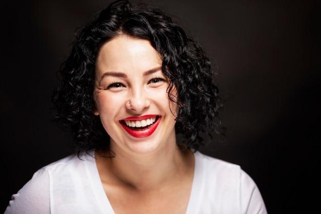 La bella giovane donna con i denti bianchi lisci sta ridendo. bruna brillante con i capelli ricci Foto Premium