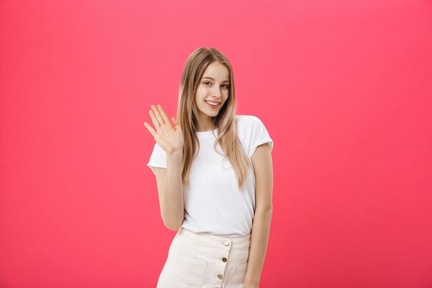 La bella giovane donna dice ciao isolata su fondo rosa Foto Premium