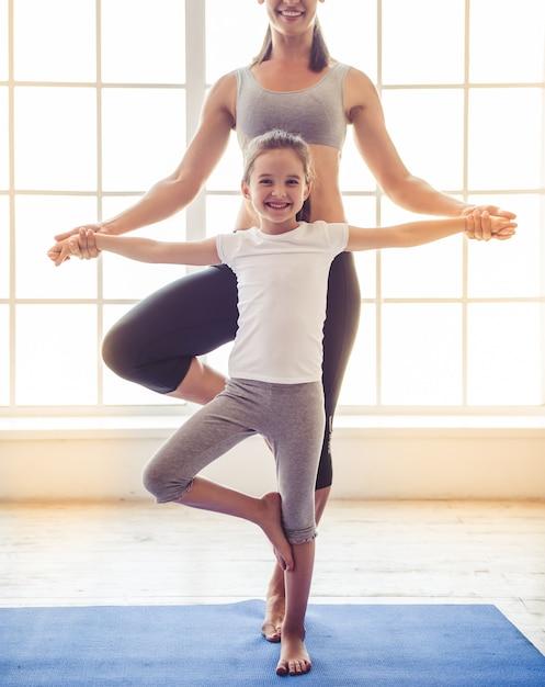 La bella giovane donna e la bambina affascinante stanno sorridendo Foto Premium
