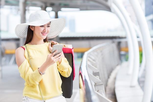 La bella giovane donna felice gode di di comperare con il sacchetto della spesa e Foto Premium