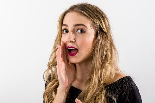 La bella giovane donna guarda da parte e tiene il suo braccio in bocca come se parlasse qualcosa in un sussurro. Foto Premium