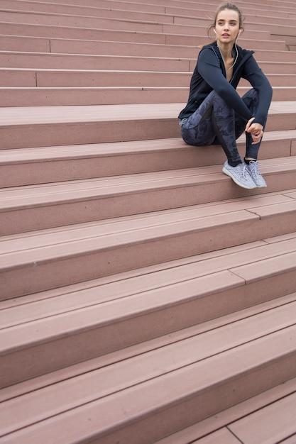 La bella giovane donna in abiti sportivi e con le cuffie che distoglie lo sguardo mentre riposano sulle scale durante la mattina funziona Foto Premium