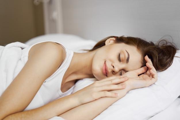 La bella giovane donna nel suo bellissimo letto bianco come la neve rilassa e rilassa, bella prova Foto Premium