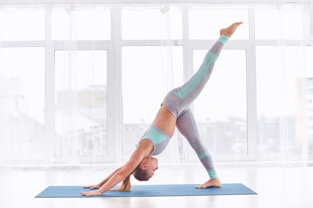 La bella giovane donna pratica lo yoga asana eka pada adho mukha shvanasana Foto Premium