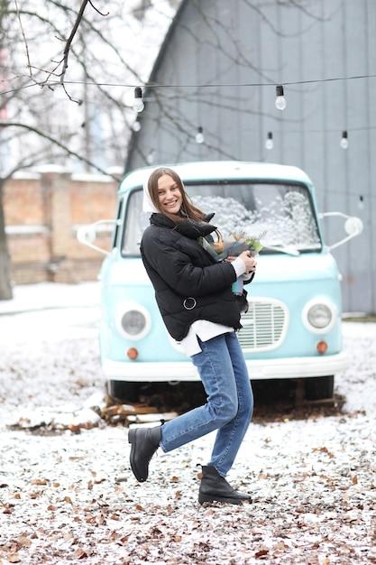 La bella giovane donna sta divertendosi vicino alla retro automobile blu nel parco dell'inverno. ragazza che tiene un mazzo di mandarini e abete rosso fatto con le sue mani. Foto Premium