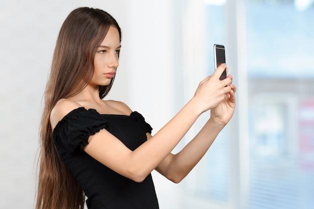La bella giovane donna sta facendo la foto del selfie con lo smartphone Foto Premium