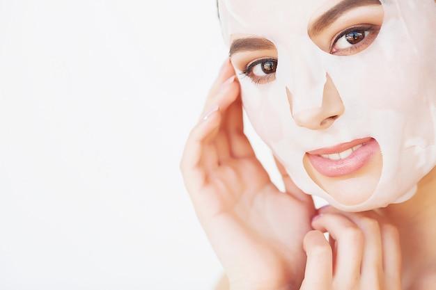 La bella giovane donna sta ottenendo la maschera facciale dell'argilla alla stazione termale, trovandosi con i cetrioli sugli occhi Foto Premium