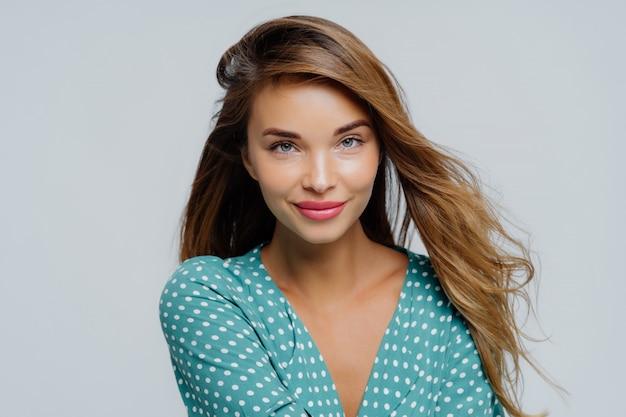 La bella giovane femmina ha il trucco, vestita in camicia polkadot Foto Premium